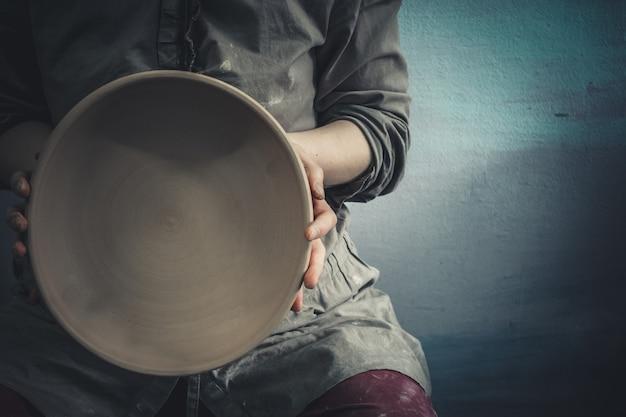 Potter segura um prato redondo de argila nas mãos