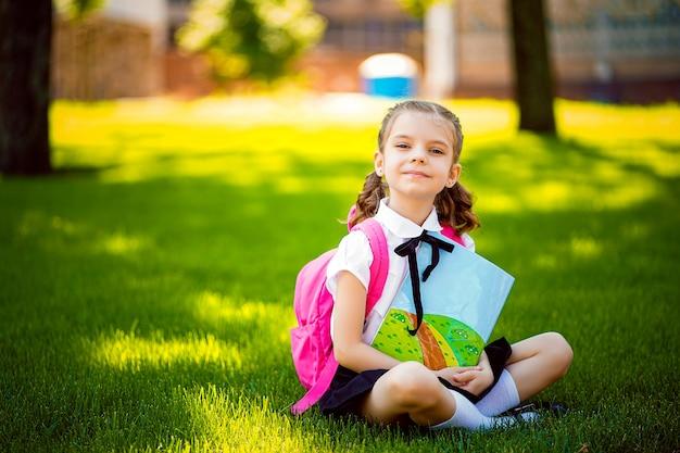 Pouca menina da escola com a trouxa cor-de-rosa que senta-se na grama após lições e leu lições do livro ou do estudo, ideias de pensamento, educação e conceito da aprendizagem.
