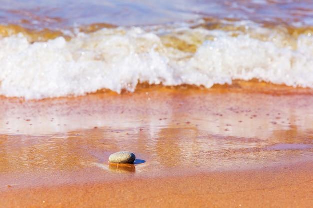 Pouca pedra na areia molhada na costa do mar. pedra e ondas com bolhas