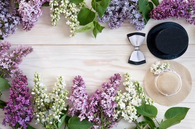 Pouco chapéu de palha, cilindro com ramos lilás em um fundo branco para o casamento,