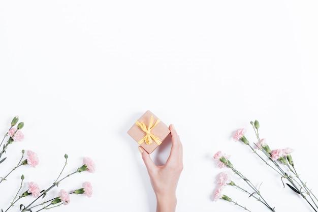 Pouco cravo rosa sobre fundo branco e a mão de uma mulher com um presente em uma caixa pequena