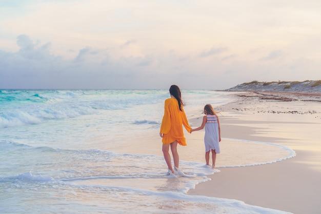 Pouco linda garota e jovem mãe na praia tropical