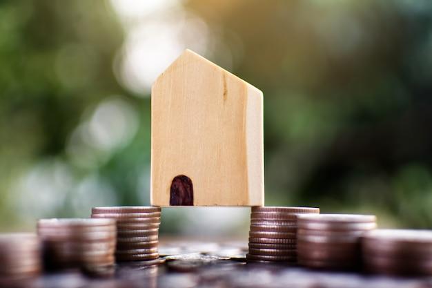 Pouco modelo da casa de madeira com moedas que salvar para residencial.