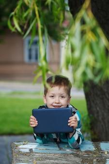 Pouco sorri menino ao ar livre usando seu computador tablet. educar e jogar