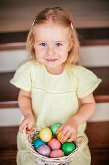 Pouco sorridente irl segurando cesta com ovos pintados e sentado na escada em casa, páscoa