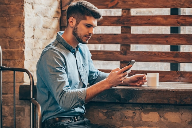 Poucos minutos para o café e uma mensagem rápida. vista lateral de um jovem pensativo segurando um telefone inteligente e olhando para ele enquanto está sentado perto da janela no interior do loft com uma xícara de café na mão