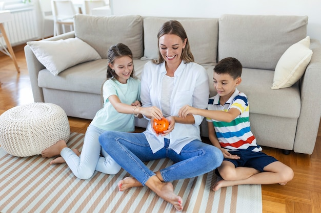 Poupança da família. jovem mãe com planejamento de orçamento de crianças, mesada das crianças. família com cofrinho.