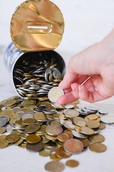 Poupança de moedas em moeda diferente, tirar o último dinheiro do cofrinho de lata durante a crise financeira, epidemia, inflação, coleta de centavos