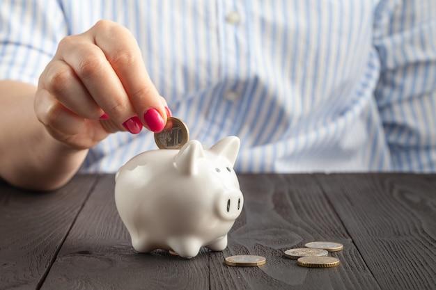 Poupança, dinheiro, seguro de anuidade, aposentadoria e conceito dos povos - próximo acima da mão sênior da mulher que põe a moeda no mealheiro