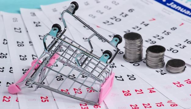 Poupança para compras. carrinho de supermercado com uma pilha de moedas em um calendário mensal