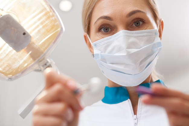 Pov close-up tiro de um dentista feminina segurando ferramentas dentárias para exame oral