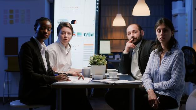 Pov de diversos empresários multiétnicos sentados à mesa de conferências discutindo a estratégia da empresa
