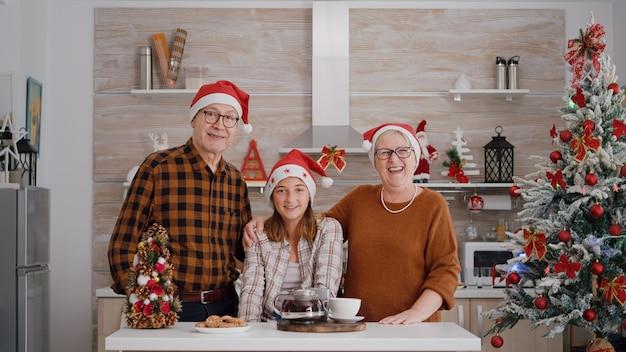 Pov de família feliz usando chapéu de papai noel cumprimentando amigos remotos durante conferência de videochamada online