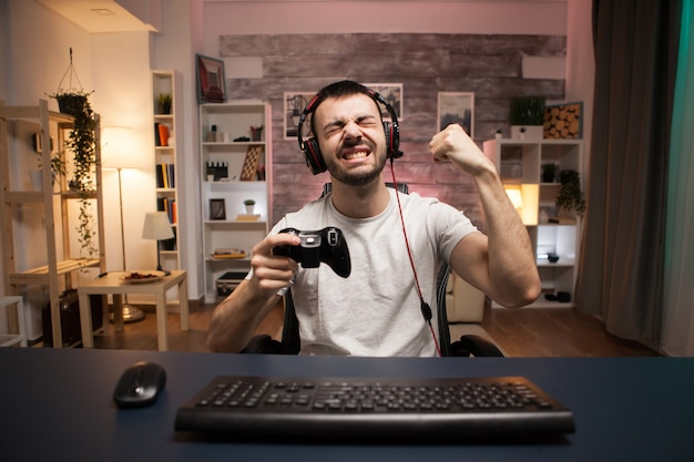 Pov de jovem feliz comemorando sua vitória no jogo de tiro online usando o controle sem fio.