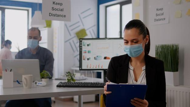 Pov de mulher de negócios com máscara médica, trabalhando no projeto de comunicação com a equipe durante a videoconferência online. empreendedor na web videochamada pela internet em um novo espaço corporativo normal