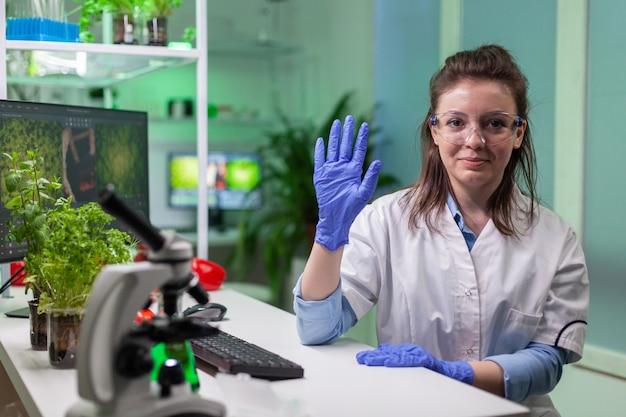 Pov de mulher química de jaleco branco analisando com equipe de biólogos
