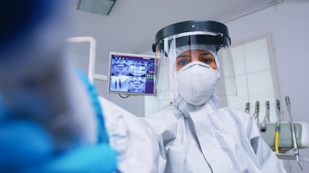 Pov paciente de dentista em traje protetor covido medindo temperatura em consultório odontológico moderno com novo normal. stomatolog usando equipamento de segurança contra coronavírus durante a verificação de cuidados de saúde da pessoa.