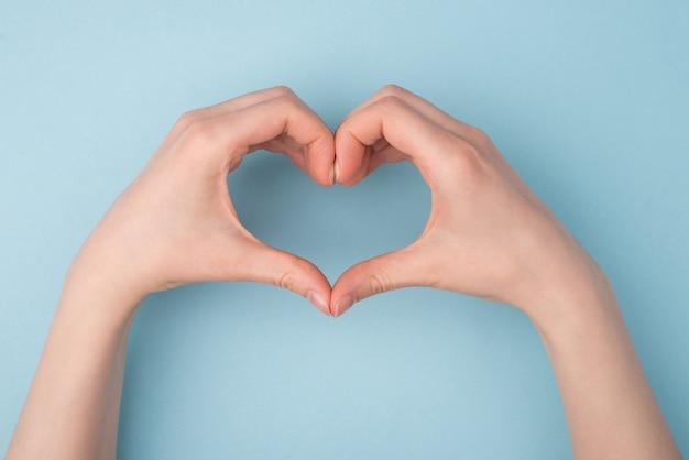 Pov superior acima de cima, close-up, foto de visualização de mãos fazendo formato de coração isolado sobre fundo de cor pastel azul