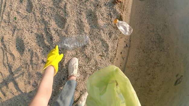 Pov tiro de jovem se abaixando para pegar uma garrafa de plástico na praia. conceito - poluição da natureza com plástico, cuidado com o meio ambiente, microplásticos