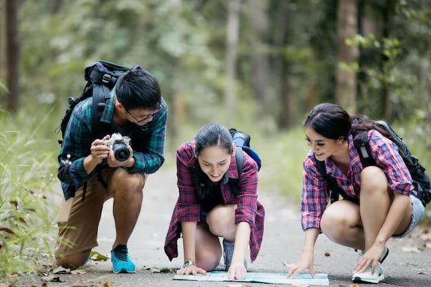 Povos asiáticos caminhadas com mochilas andando e olhando o mapa