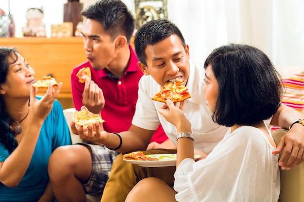 Povos asiáticos comendo pizza na festa
