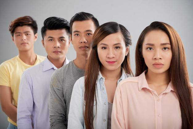 Povos asiáticos em pé em uma linha, olhando para a câmera