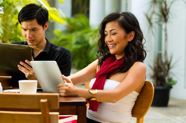 Povos asiáticos no café com computador