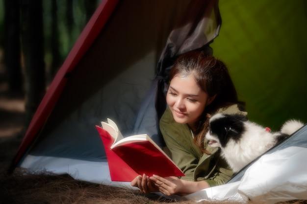 Povos asiáticos que caminham com a barraca na floresta e que acampam durante o verão no por do sol.