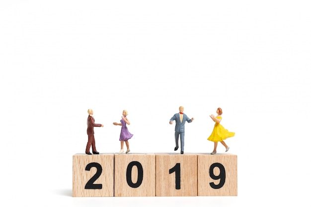 Povos diminutos que dançam no bloco de madeira número 2019.
