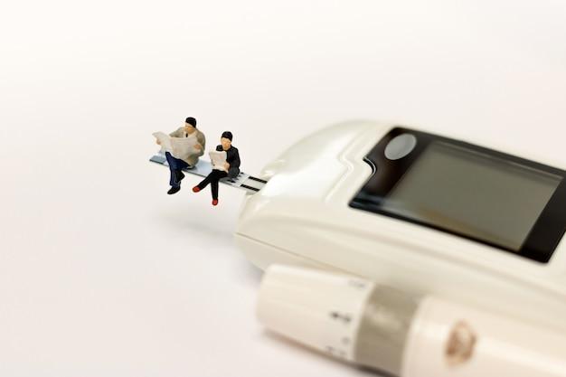 Povos diminutos que sentam-se em um medidor da glicose do diabetes, conceito dos cuidados médicos.