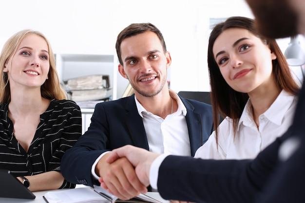 Povos do grupo de negócios apertem as mãos como olá no escritório closeup