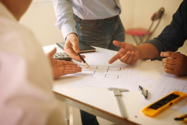 Povos do plano da construção dos trabalhos de equipa do arquiteto da reunião com modelos.