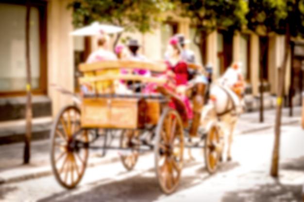Povos espanhóis borrados no vestido tradicional que monta a carruagem do cavalo ao longo da rua.