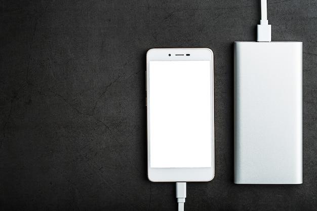 Power bank carrega seu smartphone em uma superfície escura