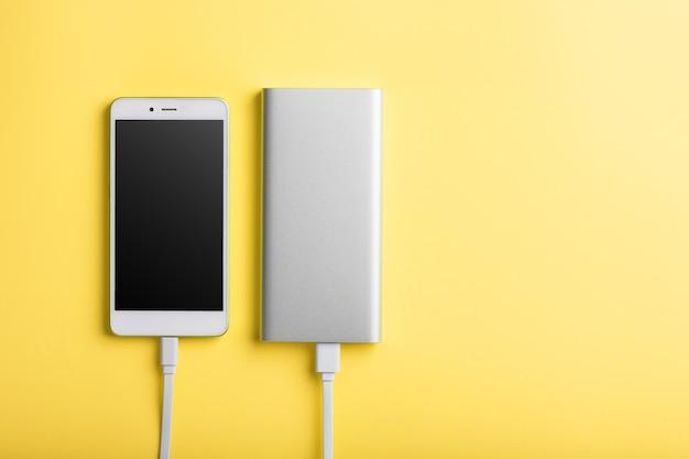 Power bank carrega seu smartphone em uma superfície roxa