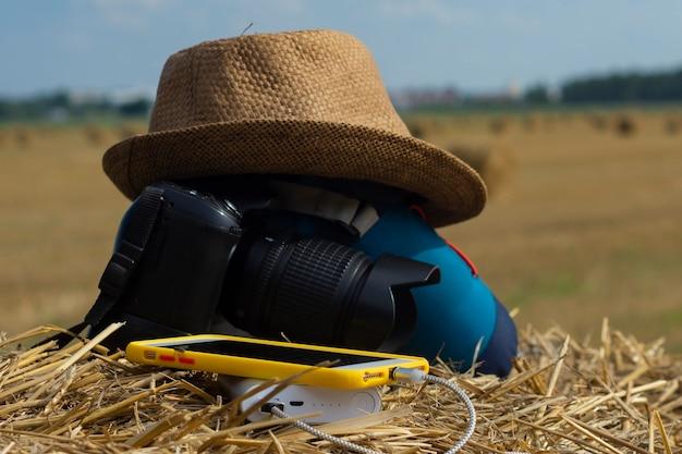 Power bank carrega um smartphone no fundo de uma câmera com uma bolsa e um chapéu sobre um fundo de feno na natureza. carregador portátil de viagem.