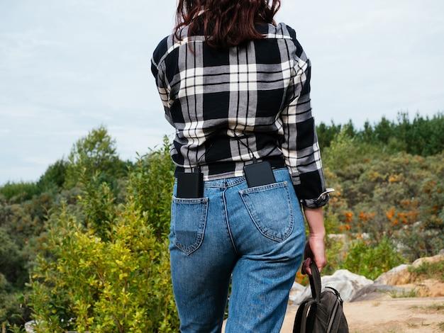 Power bank e smartphone estão nos bolsos de trás da calça jeans da menina, close-up