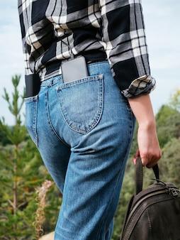 Power bank e smartphone estão nos bolsos de trás da calça jeans da menina