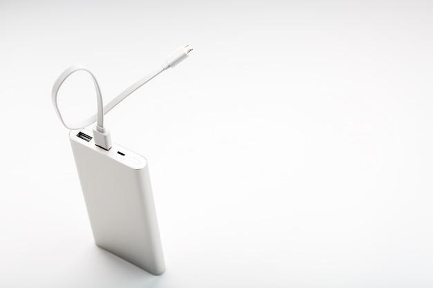 Power bank para carregar seu smartphone em um fundo branco. bateria externa universal para gadgets, espaço livre e composição minimalista.