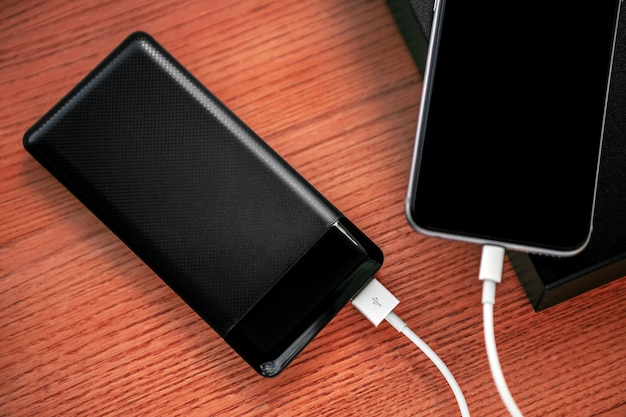 Powerbank carrega smartphone isolado em madeira