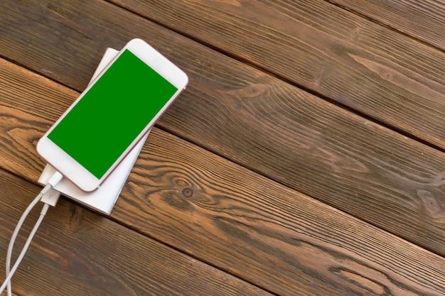 Powerbank e celular na mesa de madeira