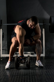 Powerlifter com braços fortes está preparando um levantamento de peso. homem musculoso treinando na academia. conceito de estilo de vida saudável.