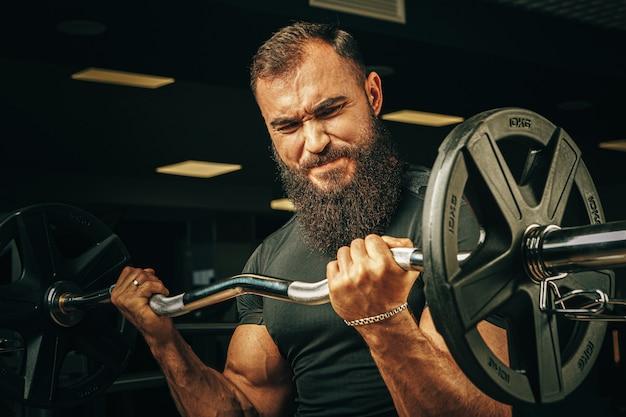 Powerlifter com braços fortes, levantando a barra em uma academia