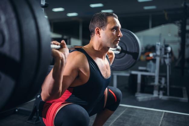 Powerlifter fazendo agachamento com barra na academia
