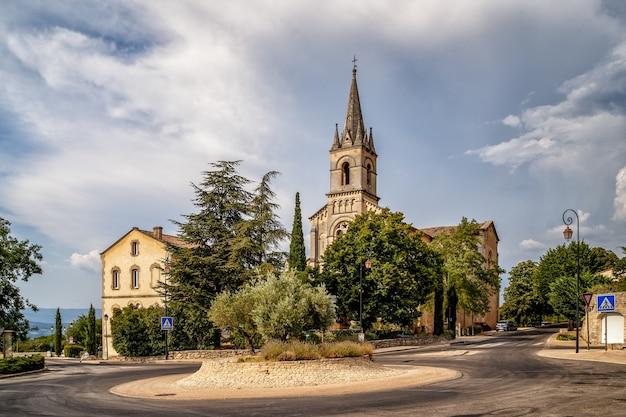 Praça central com a igreja católica da aldeia bonnieux, no departamento vaucluse provence, frança