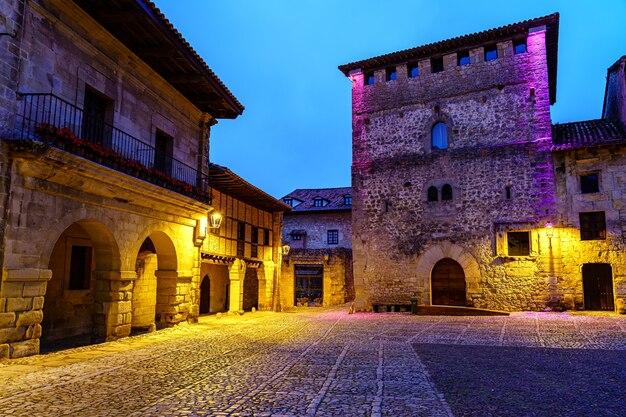 Praça da cidade velha com a torre do castelo e portas em arco, iluminadas à noite. santillana del mar.
