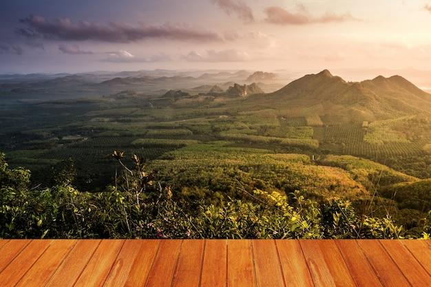 Prado com uma montanha visto de uma mesa de madeira