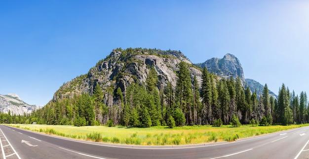 Prado e árvores cercadas por montanhas rochosas