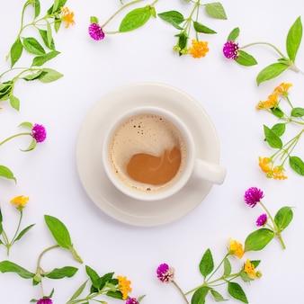 Prado e flores silvestres dispostos em círculo com copo de café plano