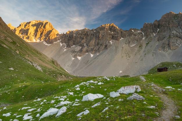 Prado e pasto alpino conjunto cordilheira de alta altitude ao pôr do sol